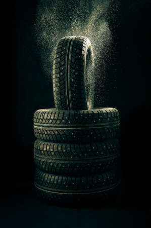 winter tyre: Snow falls on a pile of winter tyre covers