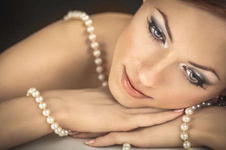 La femme de rêver avec un collier de perles sur les épaules dénudé