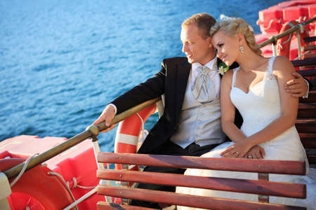 Newlyweds embracing on a boat photo