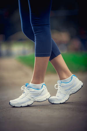 Sporting young legs in sneakers Stock Photo