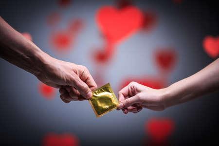 Zwei Hände, die ein Kondom Standard-Bild - 25392186