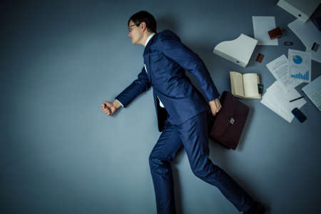 Mature businessman with briefcase in studio photo