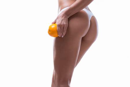 Female hips with orange on white  photo