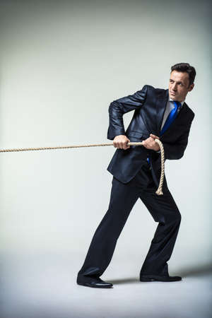 pulling rope: Mature man in suit pulling a rope