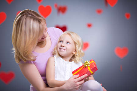 Mother and daughter with gift in studio Stock Photo - 27081063