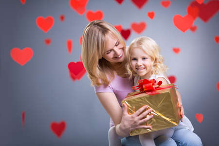 Mother and daughter with gift in studio Stock Photo - 27081072