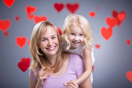 Mother and daughter with hearts in studio Stock Photo - 27081082