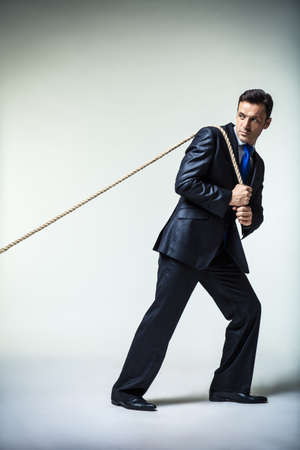 Man in suit pulling a rope photo