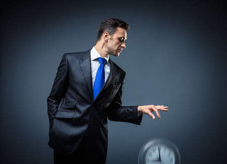 throws: Man in a suit throws clock Stock Photo
