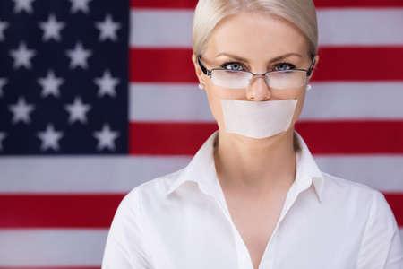 dominacion: Chica joven con su boca sellada sobre el fondo de la bandera americana