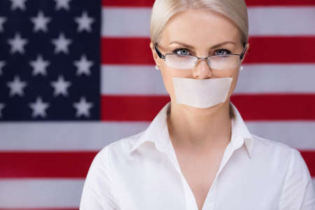 voiceless: Young girl with her ​​mouth sealed over American flag background