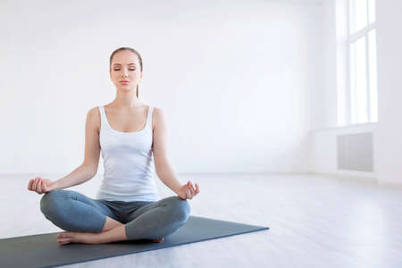 Mladá žena dělá jógu ve studiu Reklamní fotografie