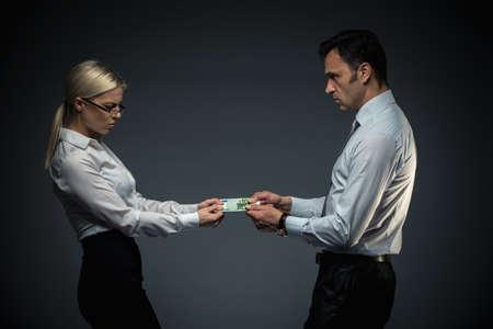 Businessman and businesswoman divide money photo