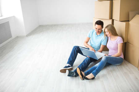 cardboard house: Young couple with laptop in the apartment Stock Photo