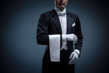 white gloves: Waiter in a tuxedo on a black background