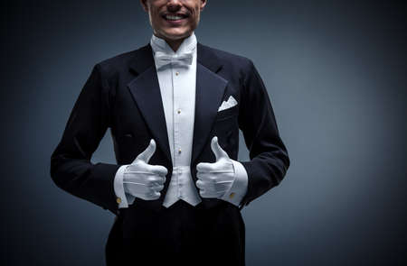 thumbup: Waiter in a tuxedo on a black background