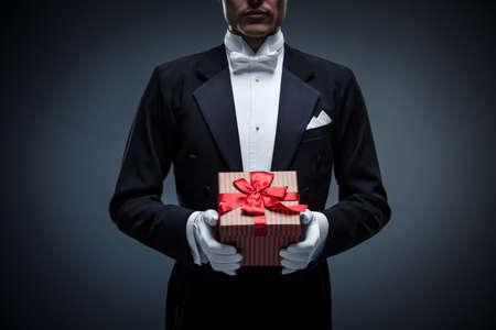 Молодой человек в смокинге с подарками