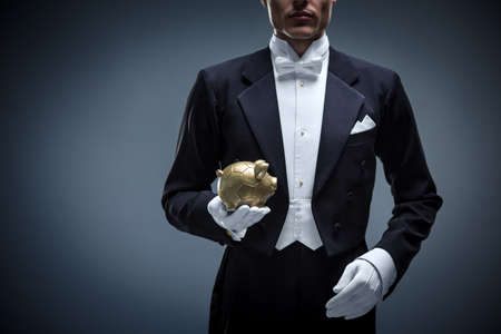 Young man in a tuxedo with piggy bank Stock Photo
