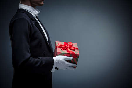 Young man in a tuxedo with a gifts Banque d'images