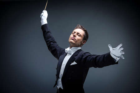 conductors: Emotional conductor in a tuxedo on a dark background