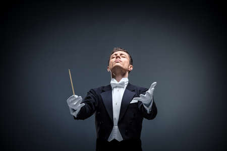 Emotional conductor in a tuxedo on a dark background