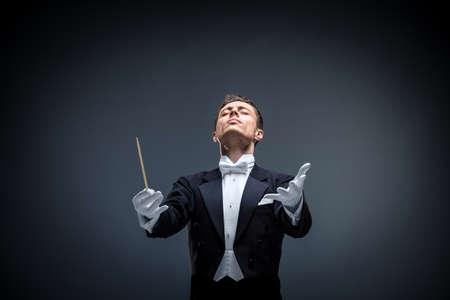 Emotionele dirigent in een smoking op een donkere achtergrond