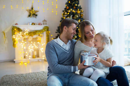 Young family with a gift at home photo