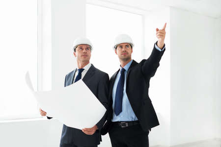 Mature architects in helmets indoor photo
