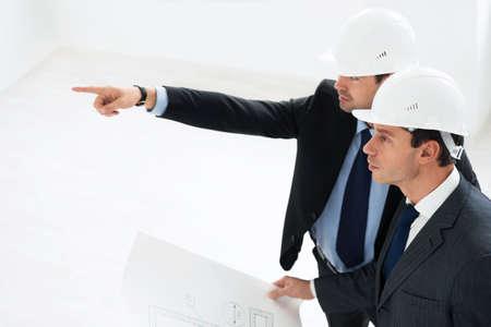 Mature architects in helmets indoor Reklamní fotografie