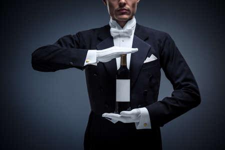 Man in a tuxedo with a bottle wine