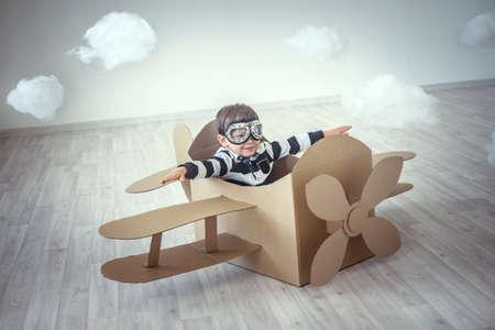 Kleine jongen in een kartonnen vliegtuig Stockfoto