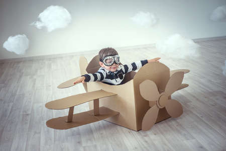 Little boy in a cardboard airplane