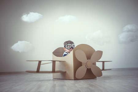 kinder spielen: Kleiner Junge mit einem Karton Flugzeug