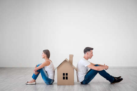 Quarreled couple with cardboard house