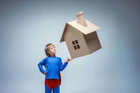 rescuer: Boy in a superman costume with cardboard house Stock Photo