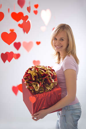Young attractive girl with a gift and hearts photo