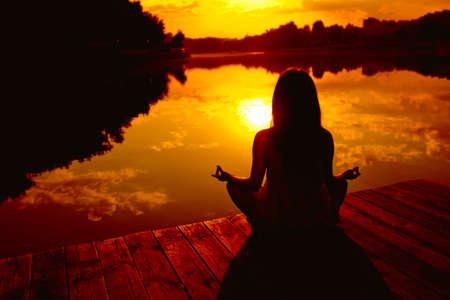 Femme faisant du yoga au coucher du soleil