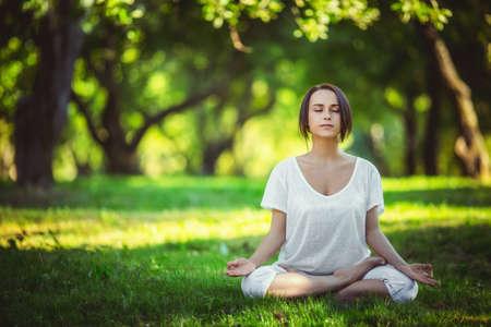 Mladá dívka dělá jógu v parku Reklamní fotografie