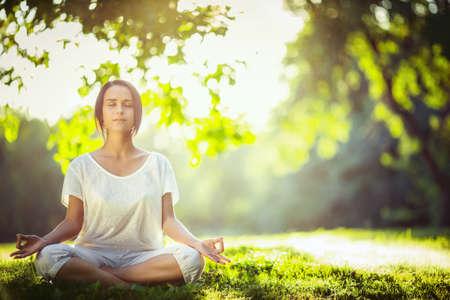 Jeune fille méditant dans le parc