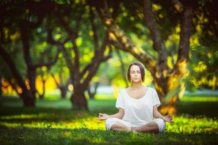 Mladá dívka meditace v parku Reklamní fotografie