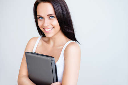 Smiling young girl with laptop photo