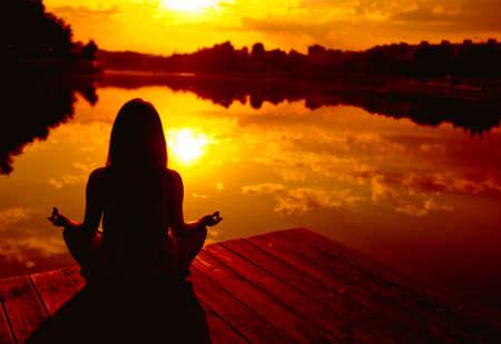 Vrouw doen yoga bij zons ondergang