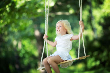 girl on swing: Little girl on a swing in the park