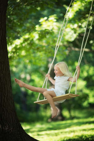 people and nature: Little girl on a swing in the park