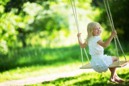 Klein meisje op een schommel in het park Stockfoto