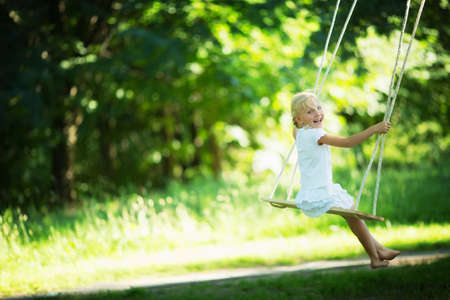 Little girl on a swing in the park