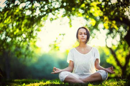 mujer meditando: Joven haciendo yoga en el parque