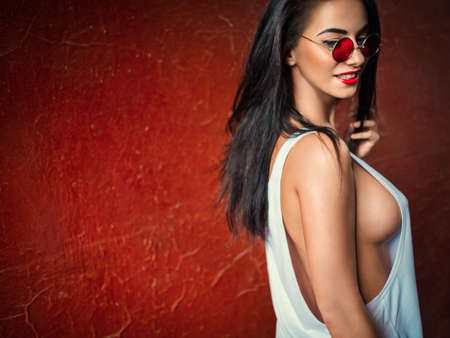 red breast: Smiling sexy girl on red background Stock Photo