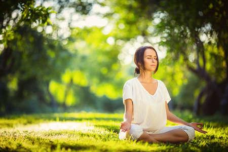 mujer meditando: Chica joven que hace yoga en el parque