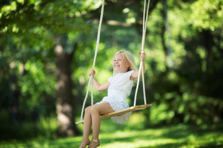 girl on swing: Little smiling girl on a swing